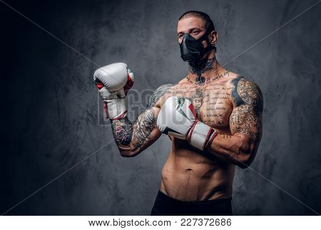 Studio Portrait Of Shirtless, Tattooed Fighter Male In A Mask Over Grey Vignette Background.