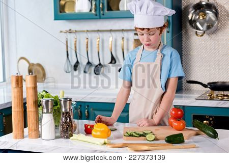 Cute Little Boy In Chef Hat And Apron Cooking In Kitchen