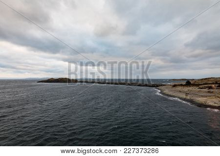 Breakwater In The Ocean At Arsvagen, Norway, Early Morning In January, With Beautiful Clouds On The