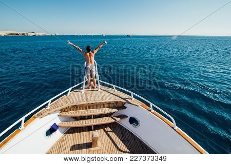 Freedom And Travel. Young Man Standing On The Deck With His Back, Raising His Hands Up Against Sea.