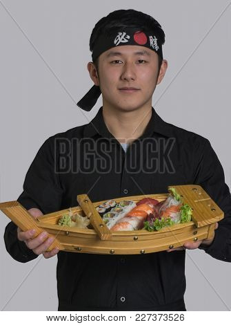 Asian cook holding a sushi Japanese food set on wood board, wearing black bandana with Chinese word translation ( Victory )