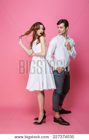 Image of young serious loving couple isolated over pink background. Looking at each other.