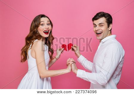 Image of young happy loving couple standing isolated over pink background holding two halves of heart. Looking camera.