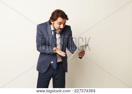Shocked Stressed Businessman Looking At Digital Tablet Screen, White Studio Background. Breaking New