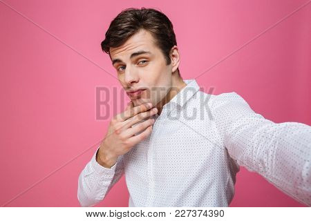 Image of young handsome man standing isolated over pink background. Looking camera make selfie.