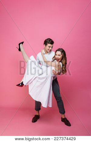 Photo of young happy loving couple having fun isolated over pink background. Looking camera.
