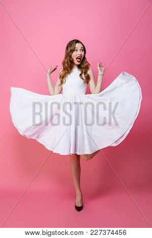 Image of cute young woman standing isolated over pink background wall. Looking aside.