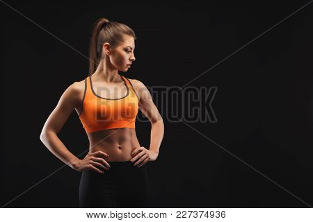 Athletic Woman Posing In Studio, Bodybuilder. Muscular Body And Strong Muscles. Shot On Black Backgr