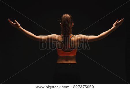 Athletic Female Fitness Model Showing Muscular Body. Studio Shot On Black Background, Low Key, Back