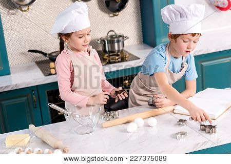 Cute Siblings In Chef Hats And Aprons Preparing Cookies Together In Kitchen