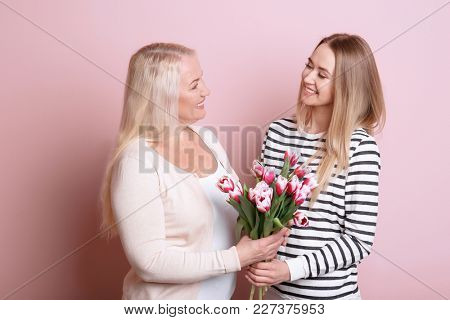 Young daughter and mother with bouquet of flowers on color background