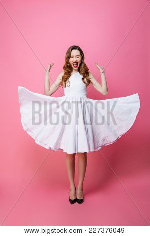 Photo of screaming young woman standing isolated over pink background wall with eyes closed.