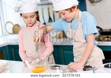 Siblings In Chef Hats And Aprons Whisking Dough In Kitchen