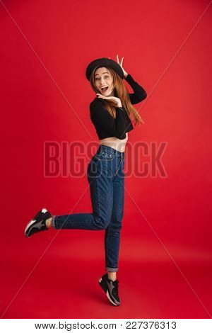 Photo of young excited woman posing isolated over red background. Looking camera.