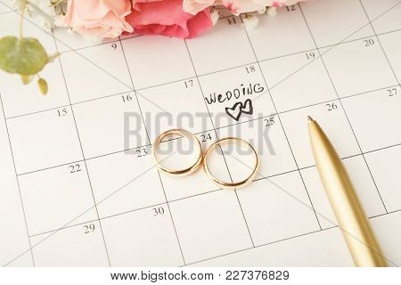 Word Wedding, Two Hearts And Gold Rings On Calendar With Sweet Rose Bouquet. Love, Invitation, Adver