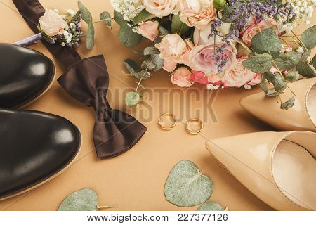 Top View Of Bride And Groom Shoes, Brown Bow-tie, Bouquet, Golden Rings, Closeup. Preparation For We