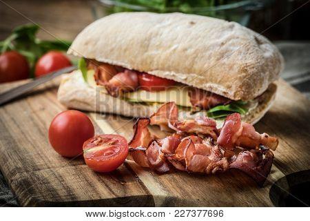 Ciabatta Sandwich With Arugula Salad, Bacon And Yellow Cheese.