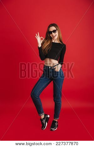 Full length portrait of a happy stylish girl wearing sunglasses showing ok gesture while standing isolated over red background