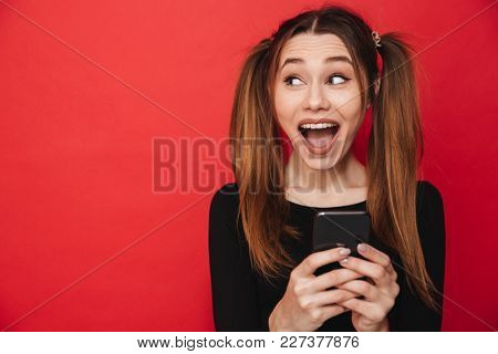 Image of young cute excited screaming lady standing isolated over red background chatting by mobile phone. Looking aside.