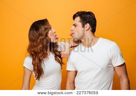 Portrait of funny man and woman in white t-shirts smiling and looking on each other with tongues sticking out isolated over yellow background