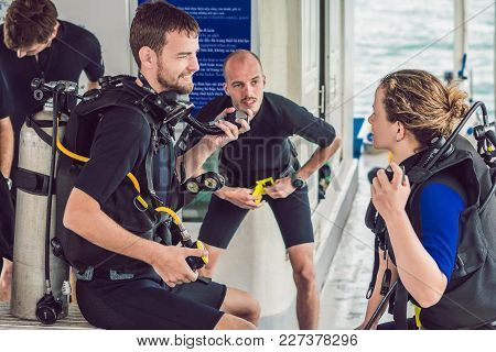 Diving Instructor Helps A Beginner Diver Prepare For Diving.