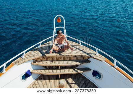 Young Handsome Man In Sunglasses Sitting At Edge Of Yacht Looking At Sea
