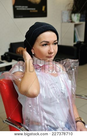 A Girl, Sits In A Hairdresser At The Stylist, With A Shuffled Head In A Towel After Washing Hair.