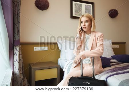 Serious Business Woman At The Hotel Room With Suitcase, Sitting On The Bed And Talking On Phone. Bus