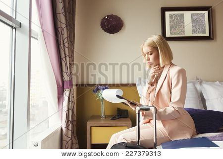 Businesswoman Reading Documents. Female Professional In Hotel Examining Papers. Business Lady Go To
