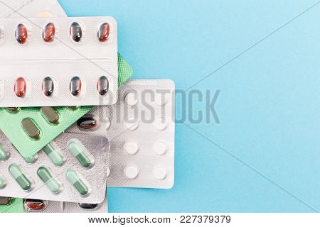 Pile Of Pill Blisters On Medical Blue Background.