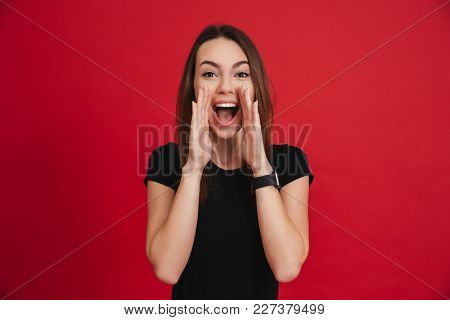 Portrait of an excited casual girl shouting isolated over pink background