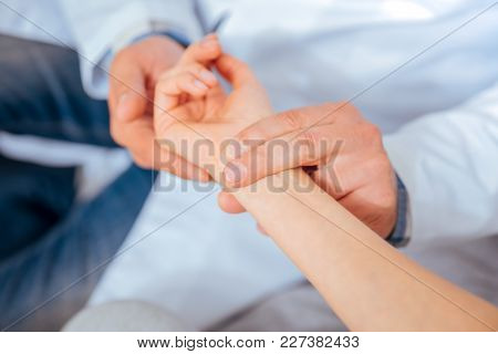 Taking Care Of Your Health. Close Up Of Medical Worker Putting His Fingers On A Wrist Of A Female Pa