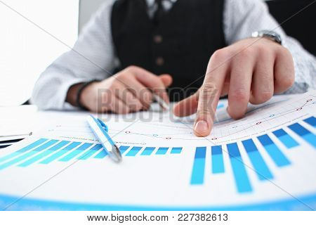 Male Arm Hold Silver Pen And Point Finger In Financial Graph Solve And Discuss Problem Closeup. Fres