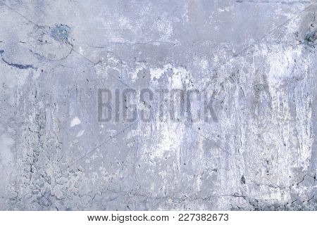 Gray Concrete Wall With Cracks And Holes. Background With An Unusual Texture.