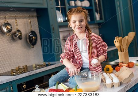 Cute Little Child Whisking Dough And Smiling At Camera In Kitchen