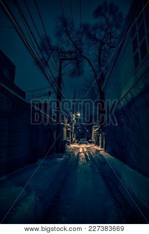 Dark urban city alley with snow in the winter at night.