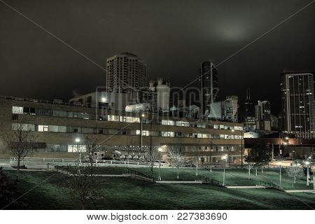Urban night scenery with a vintage factory, city park, truck, the Chicago skyline and the moon.