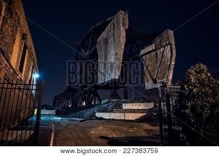 Massive industrial Chicago Bascule railroad train bridge at night.