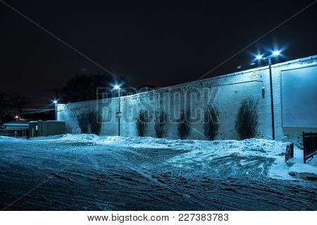 Snow filled dark city parking lot next to an industrial vintage building at night.