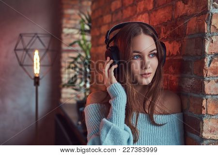 A Sensual Brunette In A Gray Sweater With Headphones Leaning Against A Brick Wall In A Room With Lof