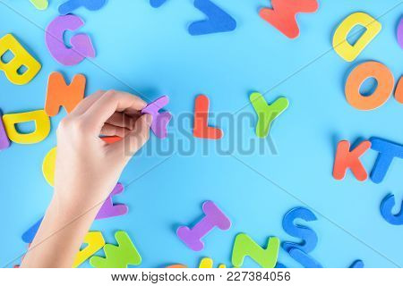 The Girl Puts Out Of The Multicolored Letters The Words Fly . Beautiful Unusual Background.