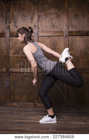 Active Female In Gym. Doing Exercises On Wooden Background.