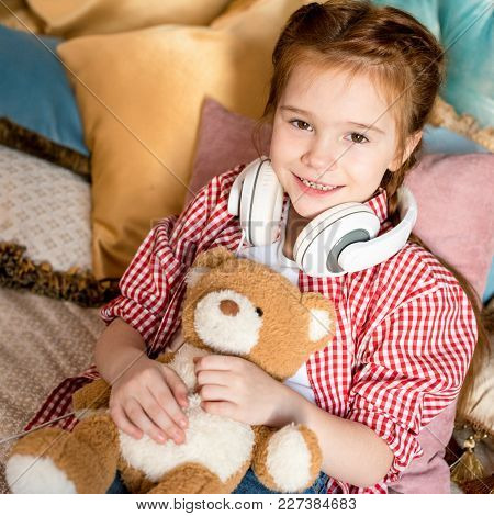 Cute Little Child In Headphones Holding Teddy Bear And Smiling At Camera