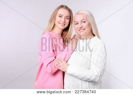Young daughter and mother on light background