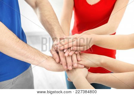 Young people putting hands together indoors. Unity concept