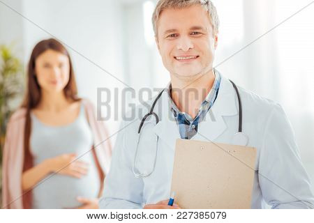 Always Ready To Help. Waist Up Shot Of A Male Pediatrician Smiling While Looking Into The Camera Wit
