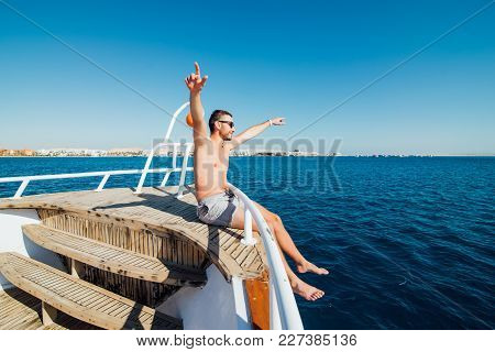 Freedom And Travel. Young Man Sitting On The Deck With His Back, Raising His Hands Up Sea