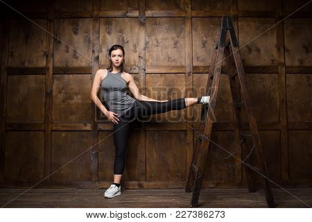 Girl In Gym. Stretching On Wooden Ladder.