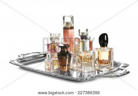 Metal tray with perfume bottles on white background