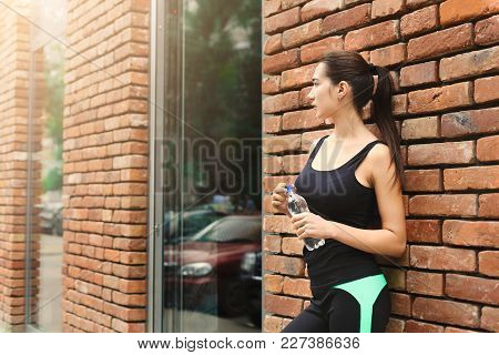 Young Woman Runner Is Having Break, Drinking Water While Jogging In City Center, Brick Wall Backgrou